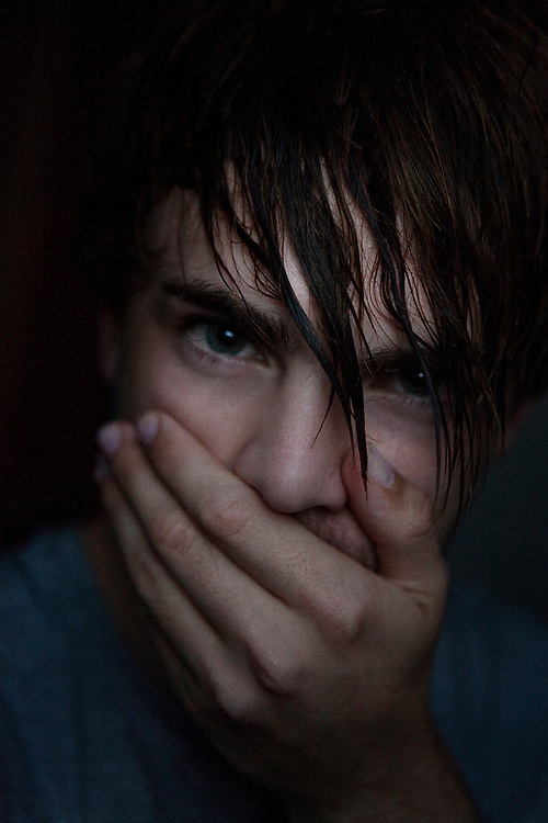 boy with his hand over his mouth. He has dark brown wet hair.