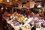 Pike Place market with vendors selling their goods, flower vendor arranging flowers