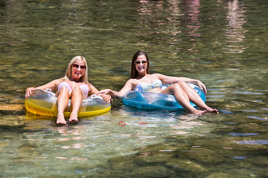 Two sexy and happy smiling tan attractive young women in bikinis suntan on colorful inner tubes at Austin's Barton Springs Spillway.
