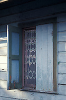Open wooden shutters of a wooden house in the town of Livingston on the Caribbean coast of Guatemala