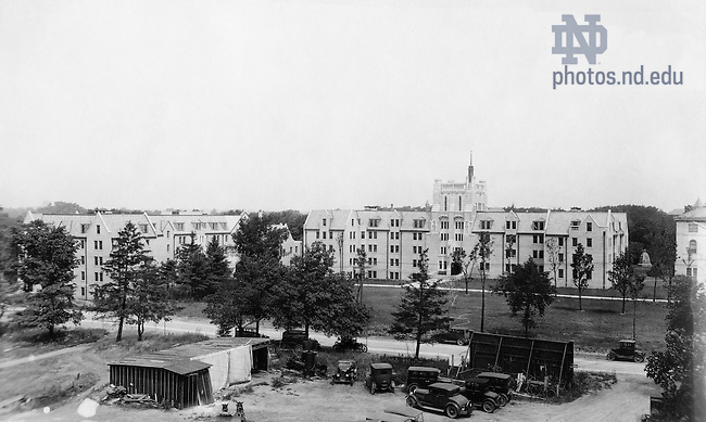 GNDL 6/06:  View of Lyons Hall and Morrissey Hall with cars in the foreground as part of the South Dining Hall construction?, c1927..Image from the University of Notre Dame Archives.