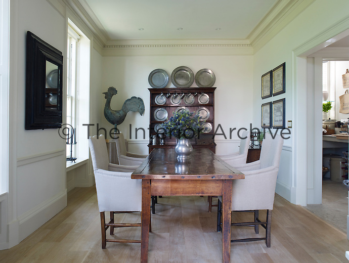 The breakfast room is furnished with a 17th century English oak table and decorated with a collection of pewter plates