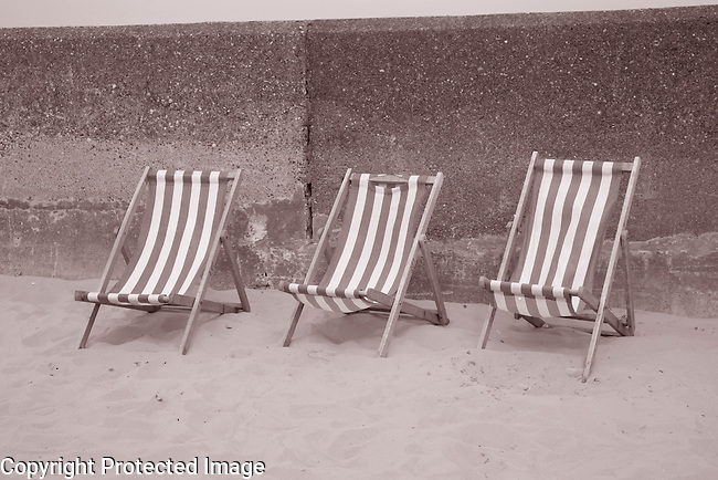 Three Green and White Striped Deckchairs on Beach