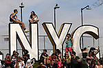 People climbed the signage to gain a better vantage point during the Governors Ball Music Festival on Randall's Island Park in New York, Friday June 5, 2015.  AFP PHOTO/TREVOR COLLENS