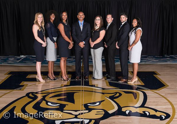 14 October 2015:  FIU's coaches and staff (pictured, left to right, Assistant Coach Brianna Skeens, Assistant Coach Keunta Miles, Assistant Coach Tiara Malcom, Head Coach Marlin Chinn, Director of Women's Basketball Operations Paige Mesalam, Athletic Trainer Mick Thompson, Strength and Conditioning Coach Jacob Talcott, and Assistant Director of Women's Basketball Operations/Video Coordinator Sydney Durrah) pose during picture day at FIU Arena in Miami, Florida.