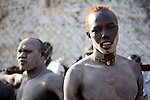 18 december 2010 - Juba, Southern Sudan - Wrestlers of the Dinka tribe from Bor, Jonglei State apply dried cattle dung before the final of South Sudan's first commercial wrestling league between their tribe and the Mundari wrestlers from Central Equatoria State at Juba Stadium. The matches attracted large numbers of spectators who sang, played drums and danced in support of their favorite wrestlers. The match organizers hoped that the traditional sport would bring together South Sudan's many different tribes. Photo credit: Benedicte Desrus