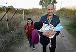 A refugee man carries one child while another follows shortly after they landed on a beach near Molyvos, on the Greek island of Lesbos, on October 30, 2015. They came on a boat full of refugees that traveled to Lesbos from Turkey. The boat was provided by Turkish traffickers to whom the refugees paid huge sums to arrive in Greece.