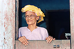 An elderly woman gazes out to the street from her front door.