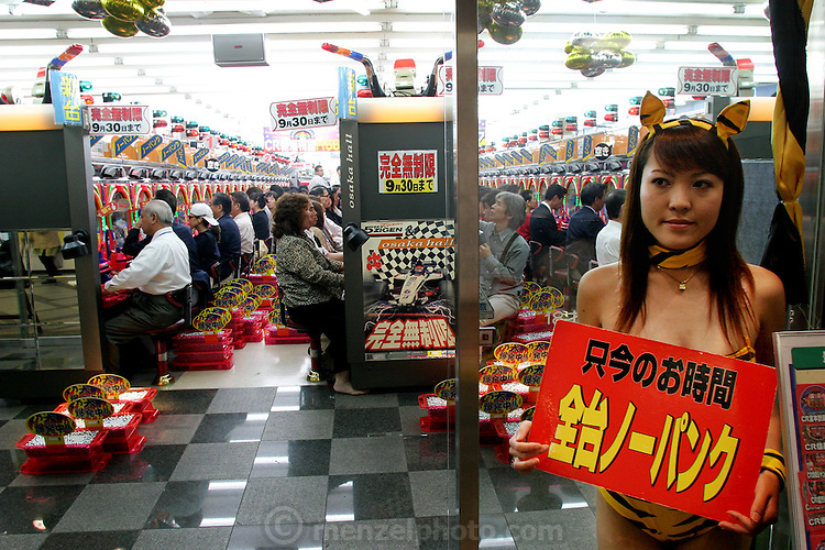 "Pachinko parlors in Japan are packed and popular with the older set. Osaka, Japan. (The girl holds a sign that says: ""right now all of the machines have 'no panku',"" which means they have turned off the part of the machine that randomly stops you from getting balls when you've started getting them. (The point of the game is to collect more and more balls, but sometimes when you get a ball somewhere, that makes them start streaming out, there is a function of the machine which will stop them after some random amount, so you usually get fewer; they've turned that function off). (Supporting image from the project Hungry Planet: What the World Eats.)"