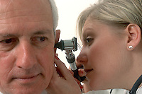 A doctor checks the ears of a mature patient during an office visit. Health care professionals.