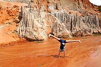 10 year old child doing a cartwheel in the red mud of the Fairy Stream (Suoi Tien), Mui Ne, Vietnam