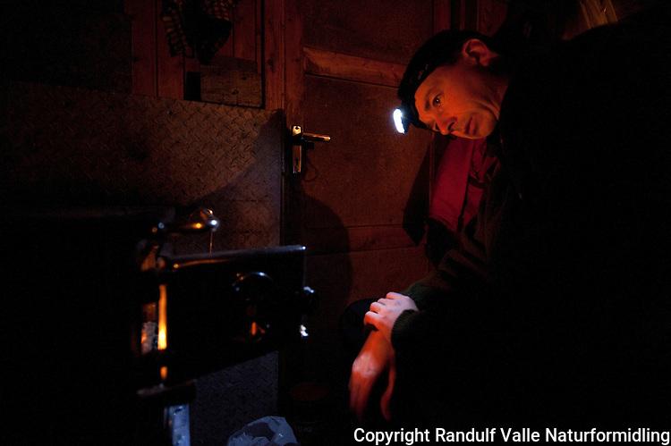 Mann fyrer i vedovn i hytte. ---- Man using wood burning stove in hut.