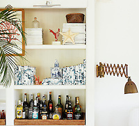 Open shelving in the living room houses a drinks tray and a shelf of books bound in blue and white wallpaper