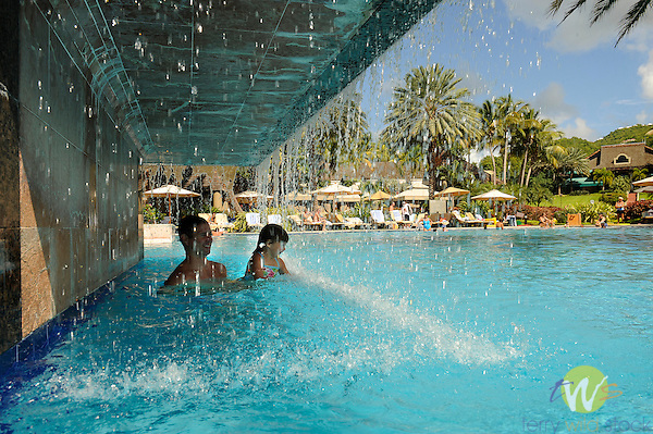 View of Westin Resort swimming pool. Father and son under waterfall