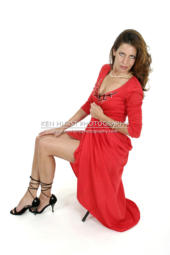 Beautiful woman in a long red dress sitting on a stool.