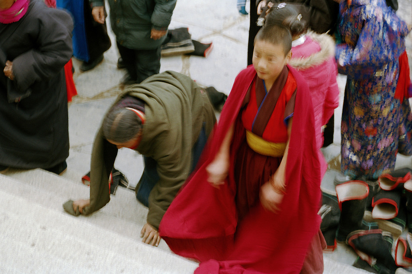 Inside the Main Assembly hall, a young monk of the Gelukpa order (Yellow Hats) is praying with pilgrims before the ceremony of the afternoon, during Monlam Chenmo, the Great Prayer. Labrang monastery, Xiahe, China, March 2 2007