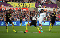 Leroy Fer of Swansea City (3rdL) crosses the ball over Nicolas Otamendi of Manchester City during the Premier League match between Swansea City and Manchester City at The Liberty Stadium in Swansea, Wales, UK. Saturday 24 September 2016