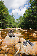 Hiking boots drying off on rocks along the North Fork East Branch Pemigewasset River in the Pemigewasset Wilderness of Lincoln, New Hampshire USA during the summer months.