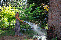 Kenna Dahleen watering her yard.