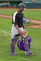 Jairo Rosario (12) of the Grand Junction Rockies carries his gear prior to warming up the starting pitcher as the Rockies played the Ogden Raptors at Lindquist Field on September 8, 2013 in Ogden Utah.  (Stephen Smith/Four Seam Images)