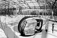 Ukraine. Province of Kiev. Pripyat. Inside a derelict amusement park, a bumper car on the side, another on the track in the snow. A big wheel. The fair ground in Pripyat meant to be opened as part of the May Day celebrations in 1986, but was never opened. The gost town of  Pripyat is inside the 30 km exclusion zone. The dead zone has been created after the catastrophe which took place on april 1986 at 1.23 am with the explosion of reactor No 4 at Chernobyl atomic power station. 3 km distant, the workers from the Chernobyl atomic power station used to live in Pripyat. The 45'000 people from Pripyat were evacuated 36 hours after the accident. The area is higly contamined by radioactive materials, like caesium 137.  © 2006 Didier Ruef ..