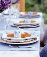 The bread rolls on each plate have been tied with a gingham ribbon and decorate with a flower for this summer lunch
