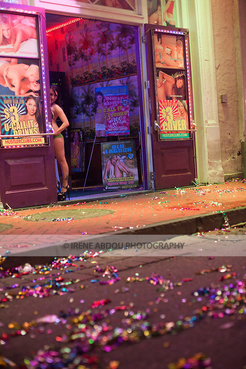 "A woman peers out from behind the doorway of an adult nightclubs on Bourbon Street in New Orleans's French Quarter.  After Madden Gras, colored ribbons line the foreground.  EA Sports, creator of the popular ""Madden NFL"" game, celebrates the release of the 2011 game edition with Madden Gras 2011, starring the New Orleans Saints.  Madden Gras 2011 culminates with a Mardi-Gras-style parade through the French Quarter of New Orleans to Jackson Square."