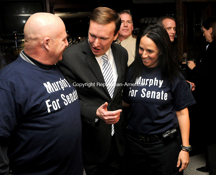 CHESHIRE, CT, 20 JANUARY 2011-012011JS08--Rep. Christopher S. Murphy, D-5th District, center, comments on tee shirts worn by Ray Soucy of Naugatuck, left, and Lisamarie Fontano of East Hampton, right, following a press conference where he announced he will run for U.S. Senate seat now held by U.S. Sen. Joe Lieberman Thursday at the Waverly Tavern in Cheshire. <br /> Jim Shannon Republican-American