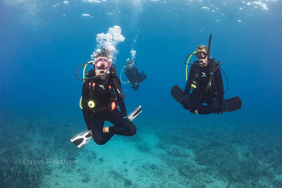 A group of three divers (MR) demonstrate neutral buoyancy skills over a reef, Hawaii.