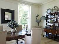 A collection of antique pewter plates is displayed on a dresser at one end of the breakfast room