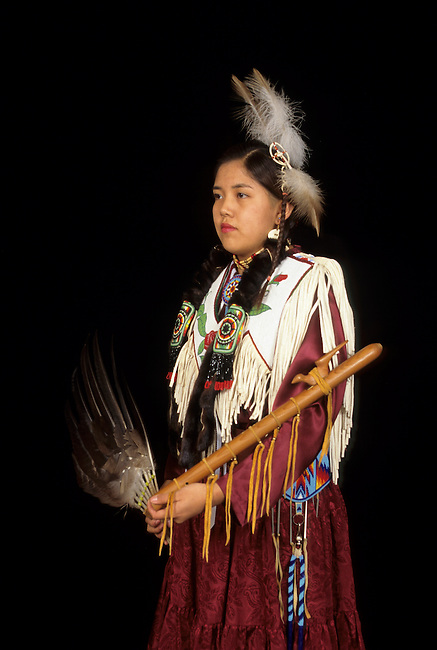 Teenage girl dressed in brain tanned hide dress decorated with beadwork with Native American wooden flute