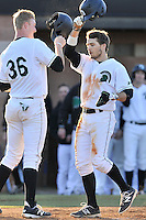 Center fielder Cody Brittain (18) of the University of South Carolina Upstate Spartans, right, is congratulated by Charlie Carpenter (36) after hitting a two-run home run in the fifth inning of a game against the George Mason Patriots on Friday, February 19, 2016, at Cleveland S. Harley Park in Spartanburg, South Carolina. (Tom Priddy/Four Seam Images)