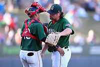 Relief pitcher Devon Fisher (44) of the Greenville Drive celebrates a save with catcher Isaias Lucena after a game against the Charleston RiverDogs on Sunday, April 29, 2018, at Fluor Field at the West End in Greenville, South Carolina. Greenville won, 2-0. (Tom Priddy/Four Seam Images)