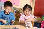 Educaton preschool  3-4 year olds fine motor literacy activity boy and girl cutting up catalogs and magazines horizontal girl talking to self