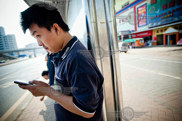 A Foxconn employee uses a smartphone as he waits for a bus opposite the factory. Foxconn is a Taiwanese technology company that makes products for Apple and Sony among others and is the largest private sector employer in China.