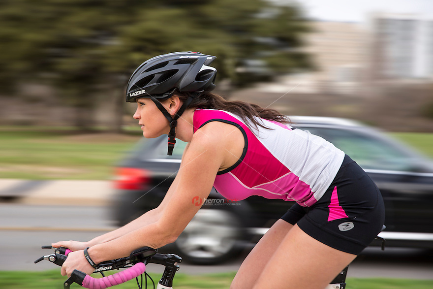 An attractive young woman rides a high-end bike/cycle training for triathlon in downtown Austin, Texas.