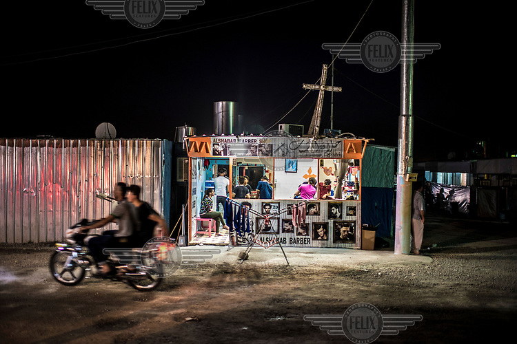Two men ride a motorbike past a barber's shop inside an IDP camp in Erbil where thousands of Christians, displaced by the advance of ISIS, have found sanctuary.