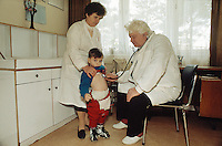 Bulgaria. Province Oblast Lovech. Lukowit. Hospital. Pediatric ward. A fat doctor, seated on a chair, checks with his stethoscope the thorax of a young skinny boy.  A nurse is holding tight the boy's shoulders. © 1997 Didier Ruef
