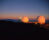 Subaru Telescope (center) and twin Keck Telescopes (right), with the partially eclipsed Full Moon setting over the shadow of Mauna Kea on the Earth's atmosphere.  Photo taken at sunrise, shortly after a total lunar eclipse.  Mauna Kea Observatory, Hawaii.
