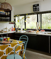 In the kitchen the table is covered in a cheerful Marimekko cloth and picture windows allow in plenty of light and views of the extensive grounds