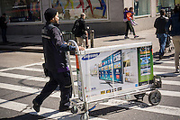 A FedEx employee delivers a Samsung brand flat-screen television in the Chelsea neighborhood of New York on Friday, March 29, 2013. (© Richard B. Levine)