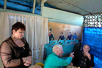 Customers talk as the proprietor of a bar in Batumi looks on..