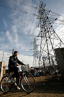 Cyclist ride past high-tension power lines in Shanghai, China. China is expected to end its power shortages as generating capacity continues to grow while demand slows, but some analysts have warned that recent heavy investment in the power sector may cause an over supply in the near future..
