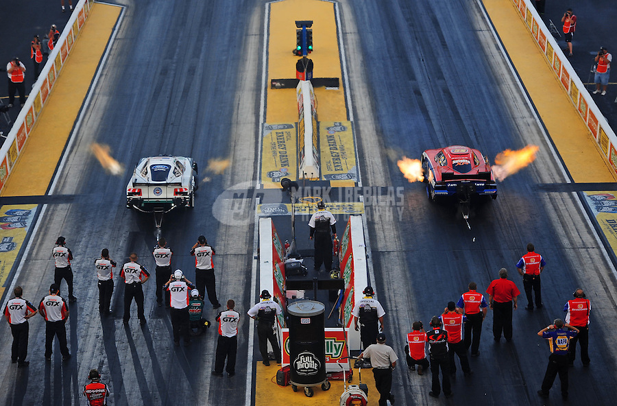 Jun. 29, 2012; Joliet, IL, USA: Crew members look on as NHRA top funny car driver Mike Neff (left) races alongside Johnny Gray during qualifying for the Route 66 Nationals at Route 66 Raceway. Mandatory Credit: Mark J. Rebilas-