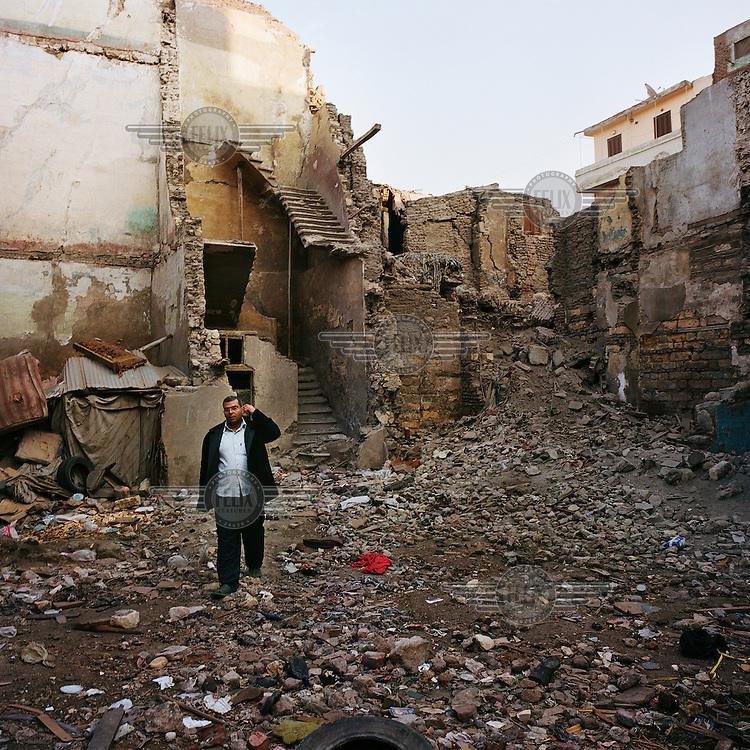A man walks across rubble, strewn between crumbling buildings.