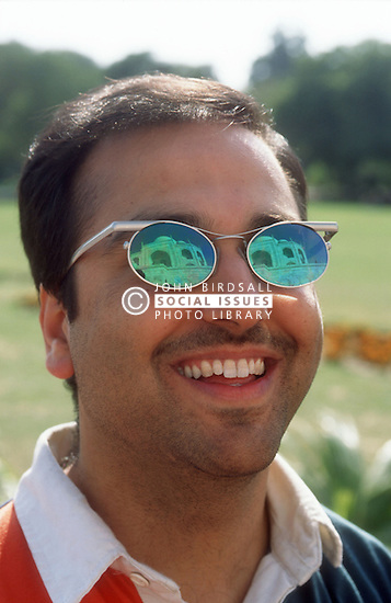 Tourist visiting the Taj Mahal; Agra; India; with the Taj Mahal reflected in his sunglasses,