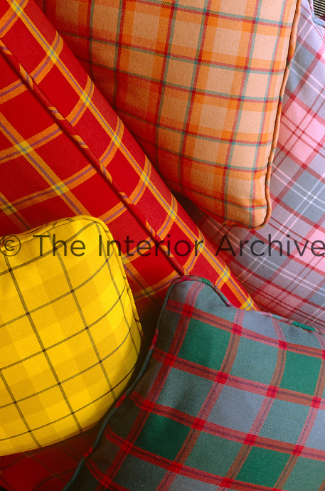 Cushions in vivid contemporary tartans piled on a sofa create a a bright and cheerful feeling in the living room