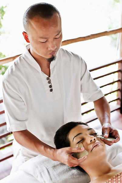 Woman Receiving Guasha Facial at Kamalaya, Koh Samui, Thailand. A woman receives a Guasha facial, a traditional Chinese medicinal practice using jade. Benefits of a Guasha facial include the reduction of fine lines, firmer skin and reduction of dark circles under the eyes.
