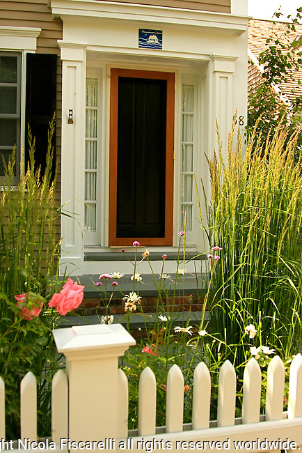 A beautiful Cape Cod doorway with a picket fence  and the garden in the foreground.