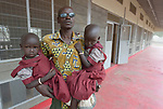 A man holds his twin daughters who are students in the Loreto Primary School in Rumbek, South Sudan. The Loreto Sisters began a secondary school for girls in 2008, with students from throughout the country, but soon after added a primary in response to local community demands.